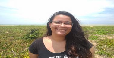 Foto da Paula, uma mulher morena com cabelos longos e pretos, em uma paisagem de restinga, com o mar ao fundo.