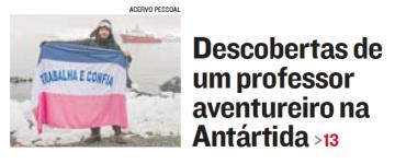 """À esquerda, há a foto do professor Rodrigo, com um gorro, segurando uma bandeira do Espírito Santo. O local é uma praia com muita neve e um navio branco e vermelho no fundo. À direita, a manchete """"Descobertas de um professor aventureiro na Antártida"""""""
